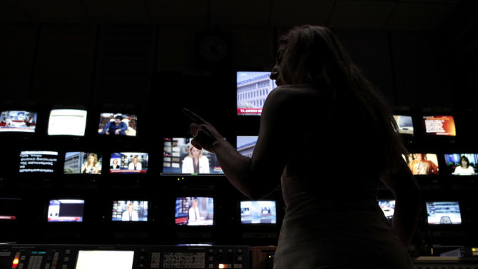 An employee of the Greece state broadcaster ERT gives instructions in front of monitors in the control room at the television station's headquarters in Athens, on Tuesday, June 18, 2013. State TV channels in Greece remained off-air Tuesday as the political storm over the future of public broadcaster ERT rages on despite a court ruling that the prime minister's decision to pull the plug was wrong. Fired ERT workers have continued live broadcasts streamed online and satellite, helped by the Geneva, Switzerland-based European Broadcasting Union, which represents the continent's public broadcasters. (AP Photo/Petros Giannakouris)