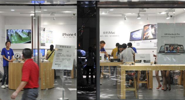 A man walks past windows of a shop masquerading as a bona fide Apple store in downtown Kunming, in southwest China's Yunnan province, Thursday, July 21, 2011. China, long known for producing counterfe