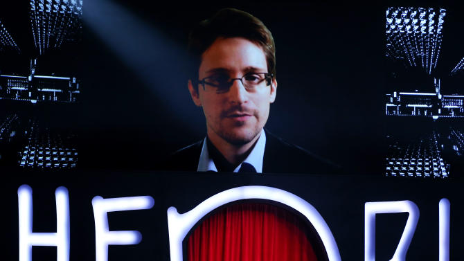A giant screen shows fugitive US intelligence leaker Edward Snowden (top) delivering a speech, on May 16, 2014 in the northern German city of Hamburg,