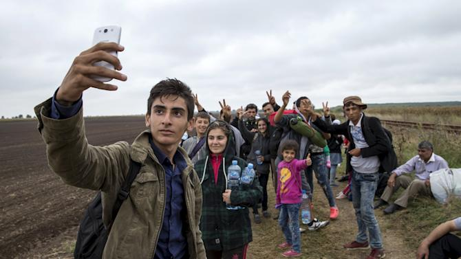 A migrant from Kobani takes a selfie with his friends as they walk along a railway track after crossing into Hungary from the border with Serbia near the village of Roszke