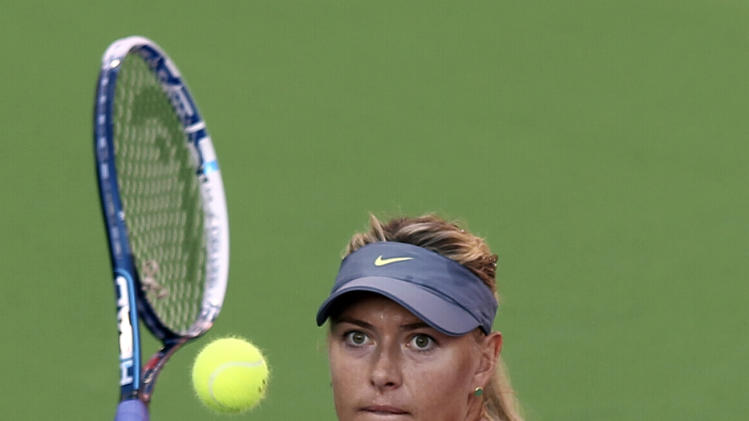 Maria Sharapova of Russia returns the ball to Samantha Stosur of Australia in the quarterfinal of the WTA Qatar Ladies Open tennis tournament in Doha, Qatar, Friday , Feb. 15, 2013. (AP Photo/Osama Faisal)