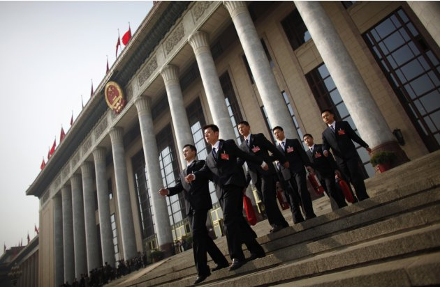 Security guards leave the Great Hall of the People, after the opening ceremony of National People's Congress in Beijing