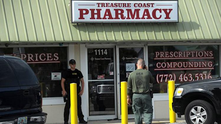 In this Tuesday, June 28, 2011 photo, agents with the Drug Enforcement Administration stand outside the Treasure Coast Pharmacy in Jensen Beach after a raid. shortly before it opened Tuesday morning as part of an ongoing investigation. DEA, the Florida Department of Health, Florida State Troopers, Martin County Sheriff's deputies and Boca Raton and Margate police participated in the investigation. (AP Photo/TCPalm.com, Alex Boerner) MANDATORY CREDIT: TCPALM.COM, ALEX BOERNER