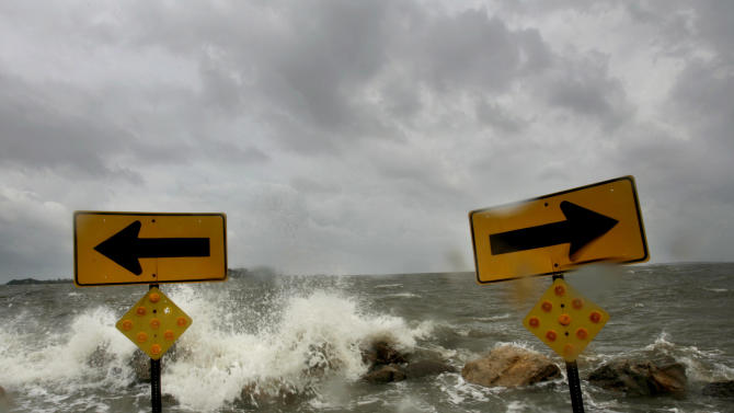 FILE - In a July 10, 2005 file photo, waves from the Gulf of Mexico pour over Cedar Key, Fla., past the road signs on G Street, as the outer bands of wind and rain related to Hurricane Dennis batter the island community.  The tough task of guessing what hurricane season will look like could be even more difficult this year for forecasters, who won't be able to rely on the relatively predictable forces known as El Nino and La Nina. So far, the National Hurricane Center in Miami is predicting that the season that begins on Wednesday, June 1, 2011, will be busier than normal, with as many as 18 named tropical storms, three to six of them becoming major hurricanes. El Nino and La Nina _ warming and cooling trends in the ocean that can either rev up hurricanes or suppress them _ are expected to be close to neutral, complicating any predictions. The last time temperatures were neutral was 2005, when hurricanes Katrina and Rita hammered the Gulf Coast with lethal results.   (AP Photo/The Gainesville Sun, David Massey, File)