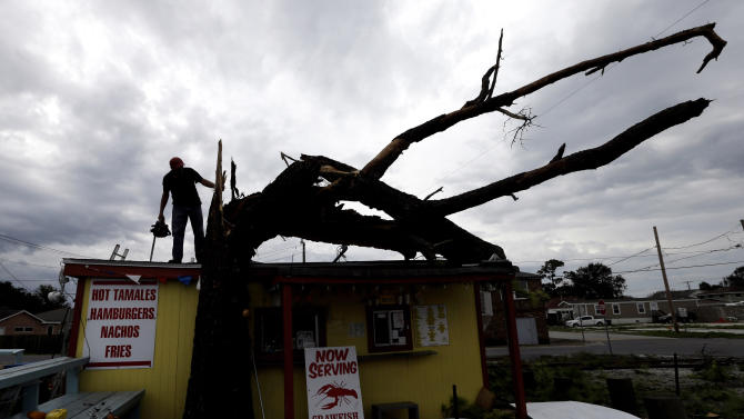 Lonney Sciortino prepares to cut down a tree which fell on top of his tamale stand during Isaac in Arabi, La.,Thursday, Aug. 30, 2012. Isaac's maximum sustained winds had decreased to 45 mph and the National Hurricane Center said it was expected to become a tropical depression by Thursday night. The storm's center was on track to cross Arkansas on Friday and southern Missouri on Friday night, spreading rain as it goes. (AP Photo/David J. Phillip)