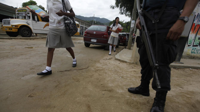 Students walk past a policeman guarding a school at an impoverished neighbourhood in Acapulco