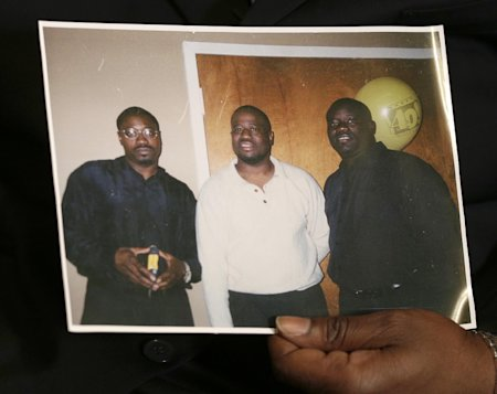 In this April 8, 2015 photo, Anthony Scott holds an undated photo that shows himself, center, and his brothers Walter Scott, left, and Rodney Scott, right, as he talks about Walter at his home near North Charleston, S.C. Walter Scott was killed by a North Charleston police officer after a traffic stop on Saturday, April 4, 2015. The officer, Michael Thomas Slager, has been fired and charged with murder. (AP Photo/Scott Family)