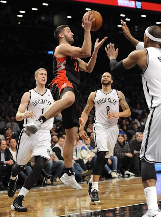 Toronto Raptors' Greivis Vasquez (21) leaps into the air to try to pass the ball around Brooklyn Nets' Mason Plumlee (1),  Deron Williams (8) and Paul Pierce (34) in the     half of an NBA bas