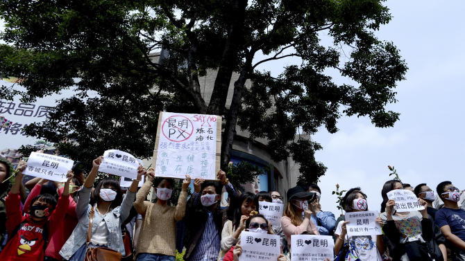 "Chinese people wear face mask with words flashing ""No to PX, paraxylene, get out of Kuming"" take part in a protest against a planned refinery project in downtown Kunming in southwest China's Yunnan province Saturday, May 4, 2013. After word spread about an environmental protest that was planned for Saturday in the central Chinese city of Chengdu, drugstores and printing shops were ordered to report anyone making certain purchases. Microbloggers say government fliers urged people not to demonstrate, and schools were told to stay open to keep students on campus. Meanwhile, hundreds of people - many wearing mouth masks - gathered in Kunming to protest a planned refinery project in the area. The demonstrators demanded information transparency and that public health be safeguarded. (AP Photo) CHINA OUT"
