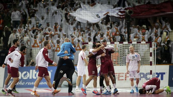 Qatar's players celebrate after their round of 16 match against Austria in the 24th men's handball World Championship in Doha