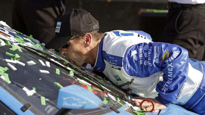 Scott Pruett kisses the windshield of the Ganassi Racing BMW Riley that he helped drive to win the Grand-Am Series Rolex 24 hour auto race at Daytona International Speedway, Sunday, Jan. 27, 2013, in Daytona Beach, Fla. (AP Photo/John Raoux)