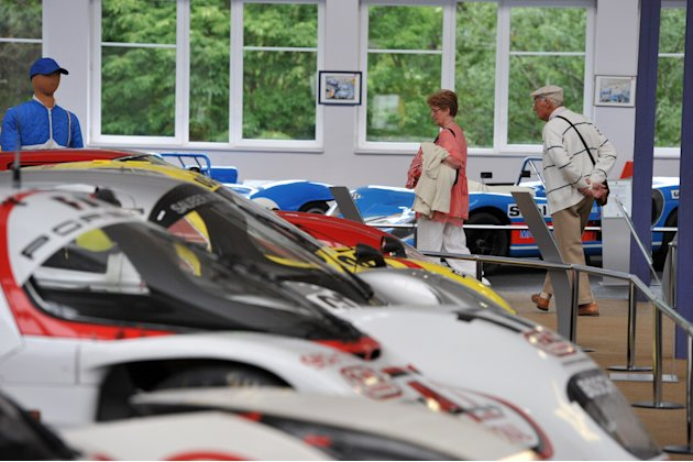 Visitors look at classic racing cars on
