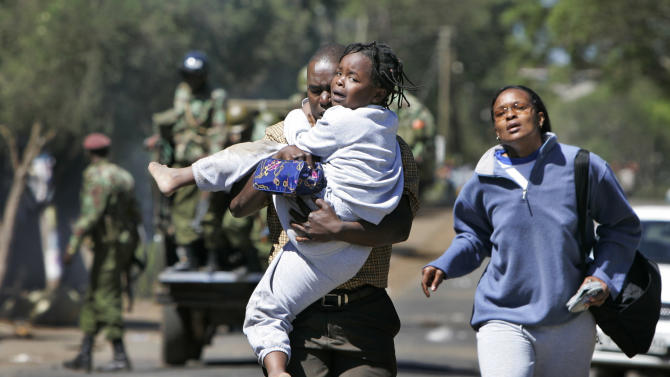 FILE - In this Thursday, Jan. 3, 2008 file photo, a young girl cries as she is carried by a man and woman fleeing an area of wooden kiosks which was set on fire by supporters of Raila Odinga's party, the Orange Democratic Movement (ODM), during post-election violence in the Kibera slum area of Nairobi, Kenya. Kenya's first nation-wide vote since devastating violence broke out after the nation's 2007 presidential election will be closely monitored by the international community and local observers to help ward off potential problems, officials said Monday, Jan. 28th, 2013. (AP Photo/Ben Curtis, File)