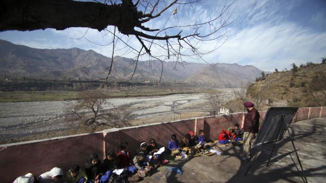 Young Indian school children study near the India-Pakistan border at the village Dallan, in Poonch, 250 kilometers (155 miles) northwest of Jammu, India, Tuesday, Jan. 15, 2013. India's army chief Gen. Bikram Singh on Monday accused Pakistan of planning an attack in which two Indian soldiers were killed in the disputed Kashmir region last week, and warned of possible retaliation. (AP Photo/Channi Anand)