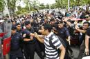 """Malaysian police struggle with supporters of opposition leader Anwar Ibrahim, after the court case outside the Palace of Justice in Putrajaya, Malaysia, on Tuesday, Feb. 10, 2015. Malaysia's top court on Tuesday upheld opposition leader Ibrahim's sodomy conviction and sentenced him to five years in prison, a verdict he slammed as the """"murder of judicial independence"""" and the result of a political conspiracy. (AP Photo/Joshua Paul)"""