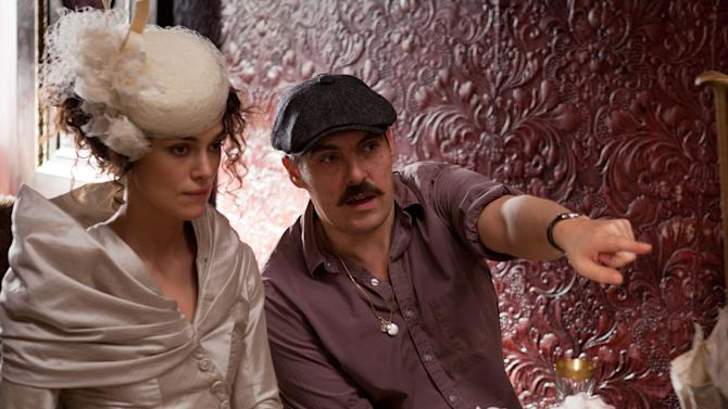"""FILE - This publicity film image released by Focus Features shows actress Keira Knightley, left, and director Joe Wright on the set of  the film, """"Anna Karenina."""" While """"Pride & Prejudice"""" and """"Atonement"""" were fresh, lively takes for an age that finds costume drama stuffy, Wright planned a wild and possibly off-putting ride on """"Anna Karenina,"""" confining most of the action to a dilapidated theater where the actors would perform in a stylized cinematic ballet without the usual grand sweep of period-drama locations. (AP Photo/Focus Features, Laurie Sparham, File)"""