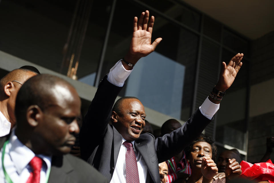 Kenyan president elect Uhuru Kenyatta waves at supporters after winning the elections in Nairobi, Kenya Saturday, March 9, 2013. Kenya's election commission posted complete results early Saturday showing that Deputy Prime Minister Uhuru Kenyatta prevailed in the country's presidential elections by the slimmest of margins, winning 50.03 percent of the vote.(AP Photo/Jerome Delay)