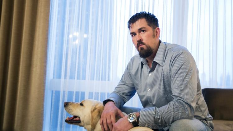 "Former U.S. Navy SEAL Marcus Luttrell poses for a portrait with his dog Mr. Rigby while promoting the film ""Lone Survivor"" in New York"