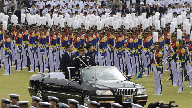 South Korean President Park Geun-hye, standing at right on the car, and South Korean Defense Minister Han Min-gu, standing at left on the car, inspect honor guard during the 66th anniversary of Armed Forces Day at the Gyeryong military headquarters in Gyeryong, South Korea, Wednesday, Oct. 1, 2014. (AP Photo/Ahn Young-joon)