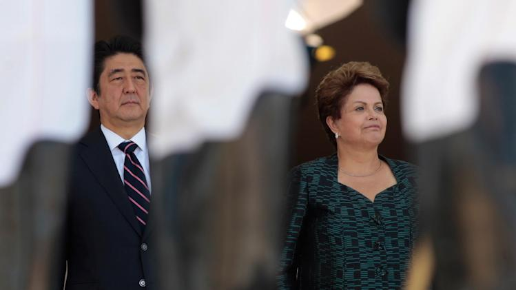 Japan's Prime Minister Shinzo Abe, left, and the Brazil's President Dilma Rousseff, stand during the playing of Japan's national anthem, during a welcome ceremony at the Planalto Presidential Palace, in Brasilia, Brazil, Friday, Aug. 1, 2014. The Japanese leader is on the last leg of his Latin American tour that included visits to Colombia, Chile and Mexico. (AP Photo/Eraldo Peres)