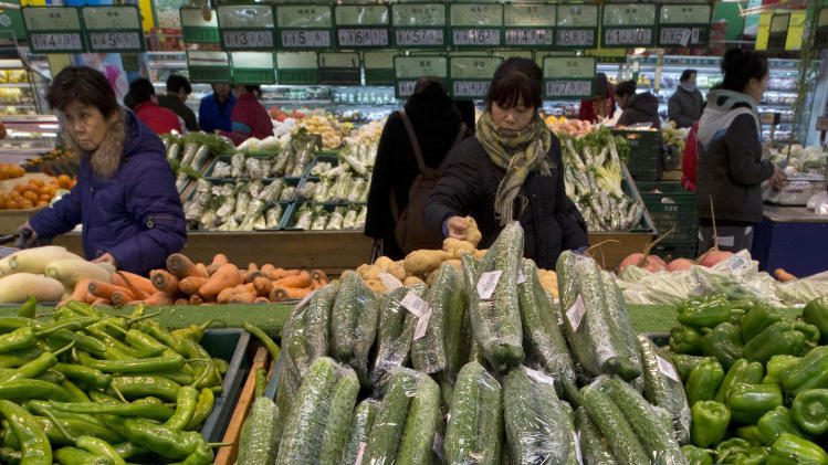 Customers shop for vegetables at a supermarket in Beijing Friday, Jan. 11, 2013. China's inflation spiked to a six-month high in December after a freezing winter pushed up vegetable prices, possibly complicating efforts to sustain a shaky economic recovery, the National Bureau of Statistics reported Friday. (AP Photo/Ng Han Guan)