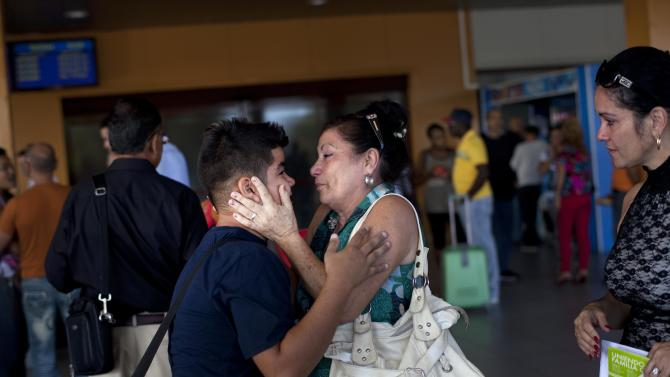 Ivan Lee, 12, says goodbye to a family member before traveling to Miami, Florida, where he will reunite with his mother who has been living there for years, as he prepares to board a plane at the Jose Marti International Airport in Havana, Cuba, Monday, Jan. 14, 2013. Cubans formed long lines outside travel agencies and migration offices on Monday, as a highly anticipated new law took effect ending the island's much-hated exit visa requirement.  The new law also extends the amount of time Cubans can remain abroad without loosing their Cuban citizenship. Before the law, Cubans had to return within 11 months, but now can remain 24 months abroad, and are eligible for extensions. (AP Photo/Ramon Espinosa)
