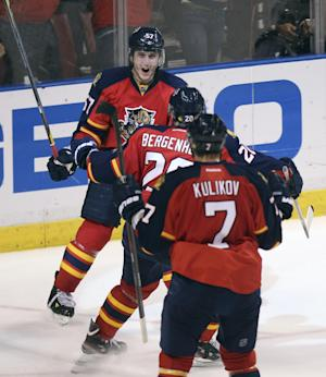 Florida Panthers' Dmitry Kulikov (7) and Sean Bergenheim (20) celebrate with Marcel Goc (57) after Goc's goal tied the score during the third period of Game 7 in a first-round NHL Stanley Cup playoff hockey series in Sunrise, Fla., Wednesday, April 26, 2012, against the New Jersey Devils. (AP Photo/J Pat Carter)