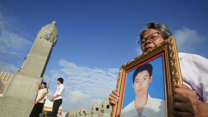 A woman holds a portrait of her family member as people offer prayers at a memorial stupa near Diamond Island Bridge during a ceremony in Phnom Penh