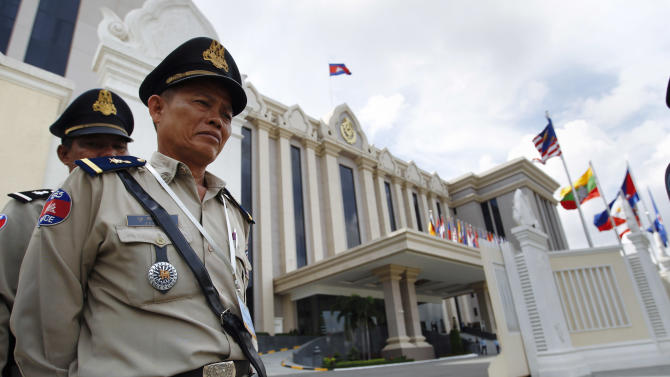 Cambodian police officers stands guard in front of the Peace Palace ahead of the ASEAN Summit and related meetings in Phnom Penh, Cambodia, Saturday, Nov. 17, 2012.  (AP Photo/Vincent Thian)