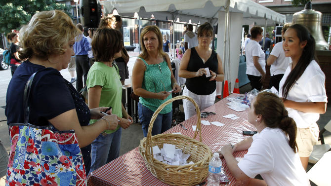 "COMMERCIAL IMAGE - Visitors to the U.S. Cellular Hello Better event take a quiz to determine if it is time to ""break-up"" with their current wireless carrier, at  Market Square on Thursday, July 19, 2012 in Knoxville, Tenn.  Relationship expert Dr. Judith Wright offered free advice on how to identify when you are in a dysfunctional relationship and how to say hello to a better experience. (Photo by Wade Payne/Invision for U.S. Cellular/AP Images)"