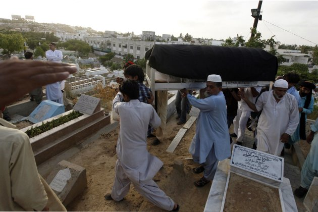 People carry the coffin of Hussain, a senior politician from Tehreek-e-Insaf political party, at a graveyard during her funeral in Karachi