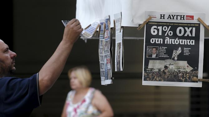 A man looks at newspapers showing the results of yesterday's referendum in central Athens