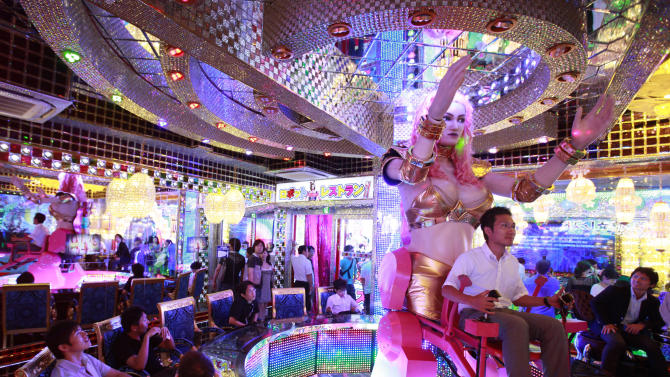 "A customer is seated on a 3.6 metre-high custom-made female robot at the newly opened ""Robot Restaurant"" in Tokyo"