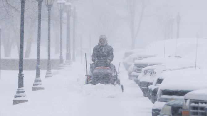 A man clears snow from the sidewalks around Friends University in Wichita, Kan. as heavy snow falls on Wednesday morning, Feb. 20, 2013. A large winter storm moved in over the early morning hours and is expected to last until Thursday evening. (AP Photo/The Wichita Eagle, Travis Heying)