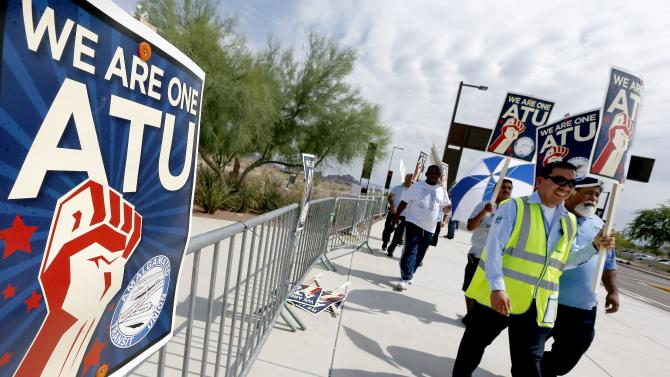 Members of the Amalgamated Transit Union Local 1433 strike in front of the First Transit Inc., bus depot on Thursday, Aug. 1, 2013 in Tempe, Ariz, after hundreds of bus operators overwhelming rejected a proposed labor contract Wednesday. The strike has affected bus service on 40 routes in Tempe, Mesa, Chandler and Gilbert, plus some routes in Scottsdale and Ahwatukee Foothills, and express service from those communities to downtown Phoenix and Scottsdale. The routes serve an estimated 57,000 bus riders daily. (AP Photo/Ross D. Franklin)