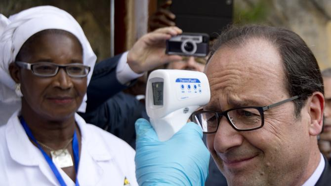 French President Hollande has his temperature measured upon his arrival at the Donka Hospital in Conakry