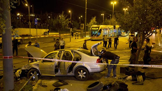 Israeli police officers inspect a car at the scene of an attack in Jerusalem, Wednesday, Oct. 22, 2014. A Palestinian motorist with a history of anti-Israel violence slammed his car into a crowded train station in Jerusalem on Wednesday, killing a three-month-old baby girl and wounding several people in what police called a terror attack. (AP Photo/Sebastian Scheiner)