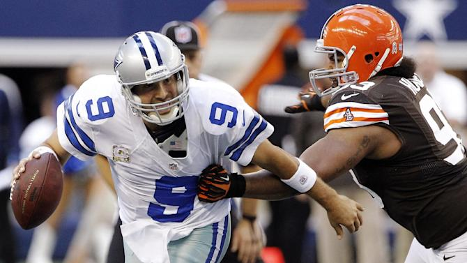 Dallas Cowboys quarterback Tony Romo (9) escapes a tackle attempt by Cleveland Browns' John Hughes (93) in the second half of an NFL football game, Sunday, Nov. 18, 2012, in Arlington, Texas. (AP Photo/Brandon Wade)