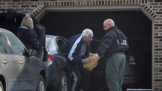 Former Penn State assistant football coach Jerry Sandusky, center, gets out of a car in front of his home Thursday, Dec. 8, 2011, in State College, Pa. Sandusky was released from jail Thursday after spending a night behind bars following a new round of child sex abuse charges filed against him. (AP Photo/Genaro C. Armas)