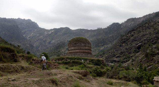 "In this May 24, 2012 photo, a villager walks to a Buddhist stupa called the ""Amlukdara,"" which was damaged by thieves looking for statues in Pakistan's Swat Valley. A team funded by the Italian govern"