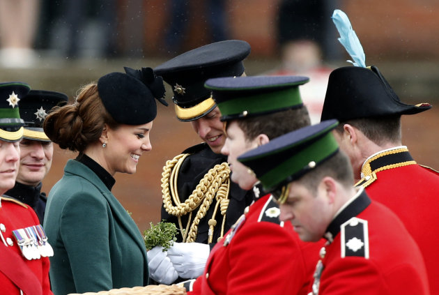 Britain&#39;s Kate Duchess of Cambridge, third left, stands with her husband Prince William, fourth left, before presenting traditional sprigs of shamrock to members of the 1st Battalion Irish Guards at the St Patricks Day Parade at Mons Barracks in Aldershot, England, Sunday, March 17, 2013. Kate presenting the sprigs of shamrocks to the regiment Sunday, follows a century-old tradition inaugurated by Queen Alexandra, the wife of the then King, Edward VII back in 1901. (AP Photo/Matt Dunham)