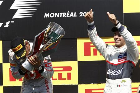 McLaren Formula One driver Hamilton kisses his trophy next to third placed Sauber's Perez during the podium ceremony following the Canadian F1 Grand Prix at the Circuit Gilles Villeneuve in Montreal
