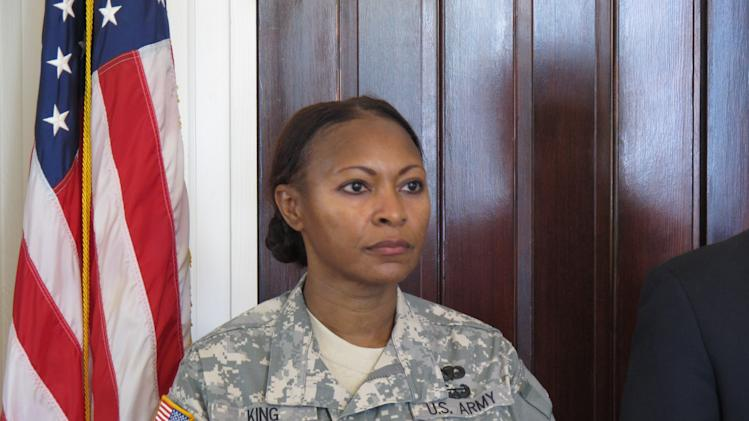 Command Sgt. Maj. Teresa King listens as her lawyer tells reporters she is getting her job back in Columbia, S.C. on Friday, May 4, 2012. King was the first woman to command the Army's drill sergeant training before she was suspended in November. Her lawyer says the Army's investigation vindicated King. (AP Photo/Jeffrey Collins)