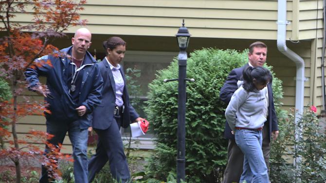 Annie Dookhan, right, is escorted to a cruiser outside her home in Franklin, Mass., Sept. 28, 2012. Dookhan is accused of faking drug results, forging signatures and mixing samples a state police lab. State police say Dookhan tested more than 60,000 drug samples involving 34,000 defendants during her nine years at the lab. Defense lawyers and prosecutors are scrambling to figure out how to deal with the fallout.  (AP Photo/Bizuayehu Tesfaye)