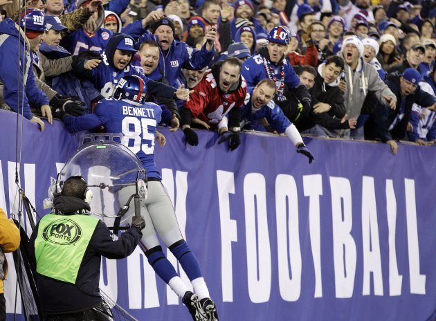 New York Giants tight end Martellus Bennett celebrates his 6-yard touchdown reception with fans during the first half of an NFL football game against the New Orleans Saints, Sunday, Dec. 9, 2012, in E