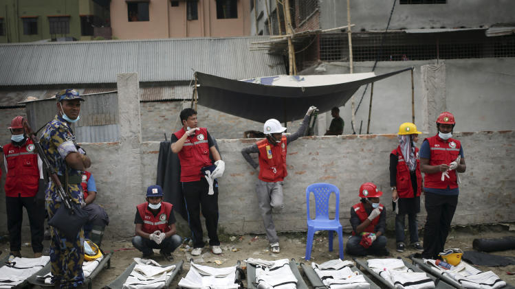 Health volunteers wait next to body bags lined up as they prepare to extract more dead bodies while workers start dislodging parts of the garment factory building which collapsed in Savar, near Dhaka, Bangladesh on Monday April 29, 2013. Rescue workers in Bangladesh gave up hopes of finding any more survivors in the remains of a building that collapsed five days ago, and began using heavy machinery on Monday to dislodge the rubble and look for bodies - mostly of workers in garment factories there. At least 381 people were killed when the illegally constructed, 8-story Rana Plaza collapsed in a heap on Wednesday morning along with thousands of workers in the five garment factories in the building.(AP Photo/Wong Maye-E)