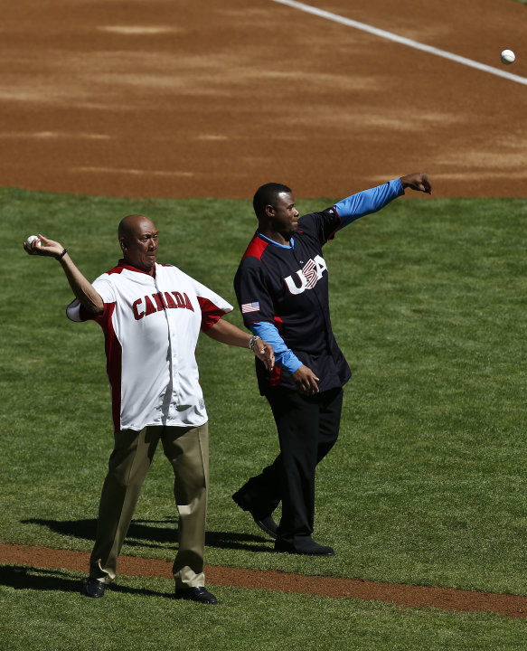 Former MLB players representing their countries Ferguson Jenkins, left, of Canada, and Ken Griffey, Jr., of the United States, throw out the first pitch prior to a World Baseball Classic baseball game