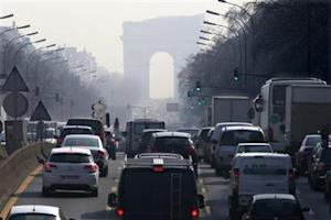 Rush hour traffic fills an avenue leading up to the Arc de Triomphe which seen through a small-particle haze at Neuilly-sur-Seine, Western Paris