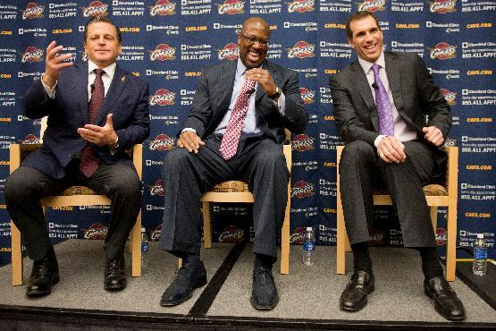 In this April 24, 2013 file photo, Cleveland Cavaliers owner Dan Gilbert, left, gestures as new head coach Mike Brown, center, and general manager Chris Grant laugh during an NBA basketball news confe