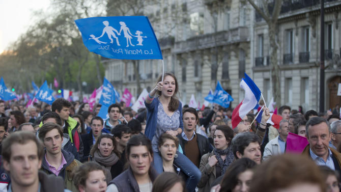 """Anti gay marriage activists wavs a flag with the logo of the movement on it during a rally to protest against the new law after French lawmakers legalized same-sex marriage, Tuesday, April 23, 2013 in Paris. Lawmakers legalized same-sex marriage after months of bruising debate and street protests that brought hundreds of thousands to Paris. Tuesday's 331-225 vote came in the Socialist majority National Assembly. France's justice minister, Christiane Taubira, said the first weddings could be as soon as June. Flags read, """"demonstration for all."""" (AP Photo/Michel Euler)"""